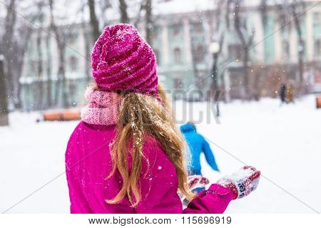 Young happy womanplay snowballs in winter city park outdoor