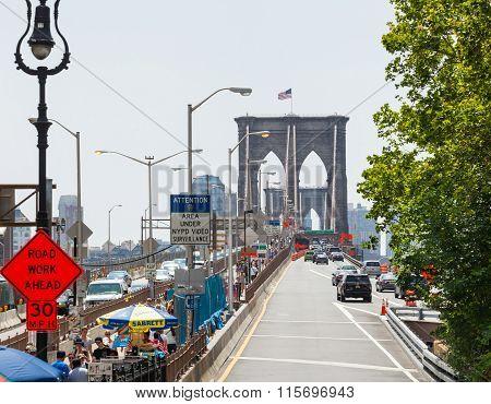 Tourists Crossing The Brooklyn Bridge