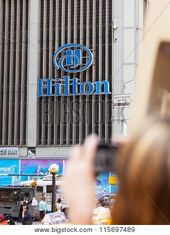 Tourist Photographing The Sign Of Hilton Hotel, Nyc.