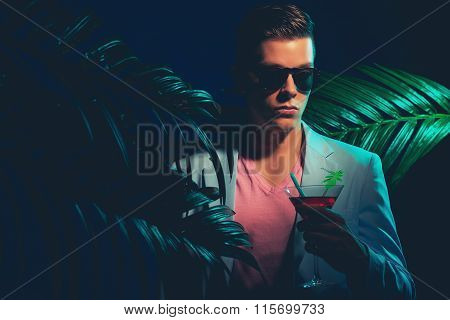 Man In Formal Suit With Drink Between Palm Leaves