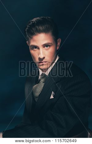 Classic Stylish Vintage Man In Suit And Tie. Hair Combed Back. Dark Blue Background. Studio Shot.
