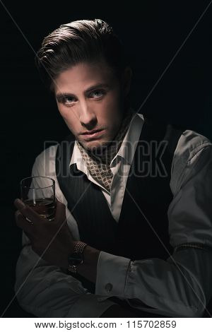 Retro Fashion Young Man With Glass Of Whiskey In Waistcoat. Greasy Hair Combed Back. Dark Blue Backg