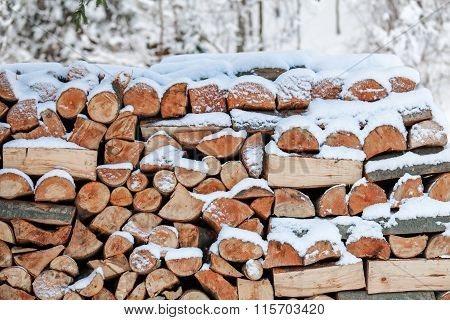 Stacked firewood and covered with snow
