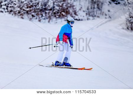 Woman in white skiing suit on mountain slope