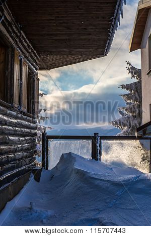 Winter Landscape Of Wooden Chalet And Cloudy Sky
