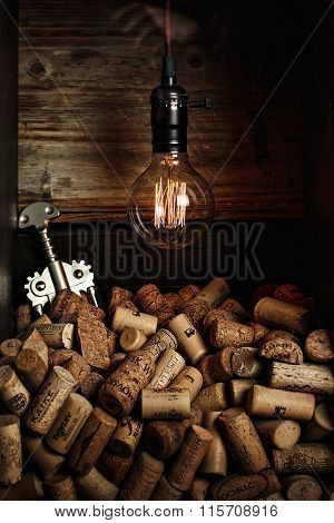 Closeup of a group of wine corks and a corkscrew on a rustic wood table and a light to dark warm bac