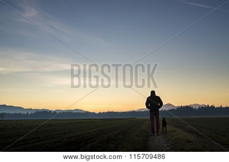 View From Behind Of A Man Walking With His Black Dog At Dusk On A Country Road