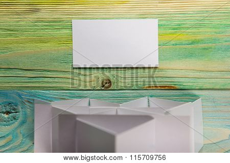 White blank business visit card, gift, ticket, pass, present close up on blurred blue background. Co