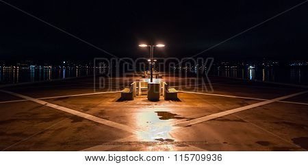 Night time on a lonely pier in Halifax, Nova Scotia.  Halifax city lights across the harbor.