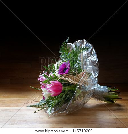 Bouquet Of  Spring Flowers In Cellophane On Wood, Dark Background, Copy Space