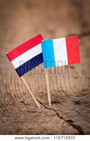 Flags of France and Netherlands on wooden background