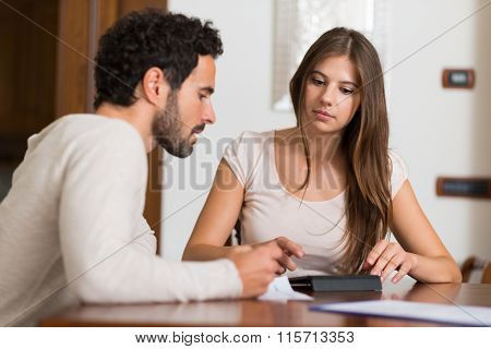 Young couple calculating their expenses. Shallow depth of field, focus on the woman
