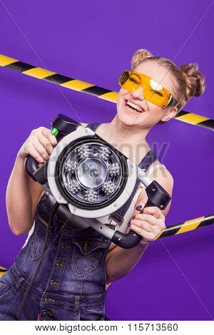 Emotional Blonde With Construction Safety Glasses On A Purple Background With A Tool For Grinding