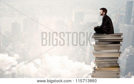 A serious businessman in elegant suit sitting on a pile of giant books in front of a grey city scape with clouds, fog