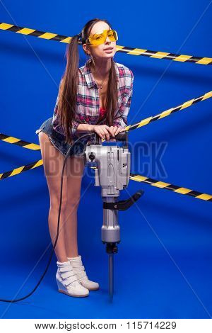 Sexy Brunette With A Jackhammer On A Blue Background In Goggles