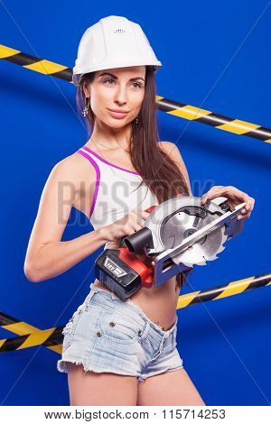 Brunette In Shorts With An Electric Jigsaw On A Blue Background With A White Ribbon In The Protectiv