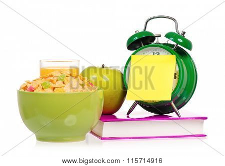 Big green alarm clock with book and breakfast, isolated on white background