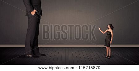 Little bussineswoman in front of a giant boss legs concept on background