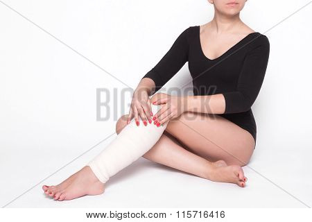 Girl On A White Background Corrects An Elastic Bandage Which Tied Her Leg