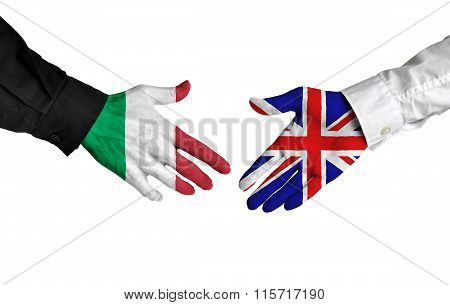 Italy and United Kingdom leaders shaking hands on a deal agreement