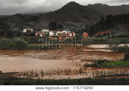 Small village on the coast of river with brown water. Madagascar
