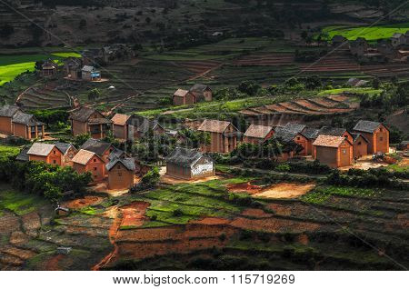 Small village on the hill with green gardens and red soil. Madagascar