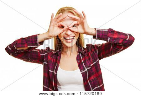 Young happy woman holding her fingers in front of her eyes as glasses