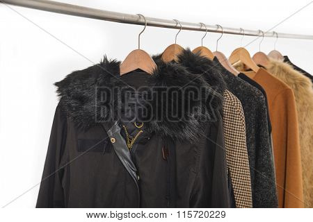 Variety of casual female clothes of different colors coat on hangers
