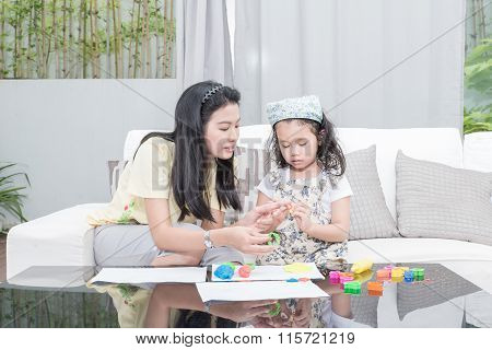 Asian mother and kid daughter playing with plasticine in home