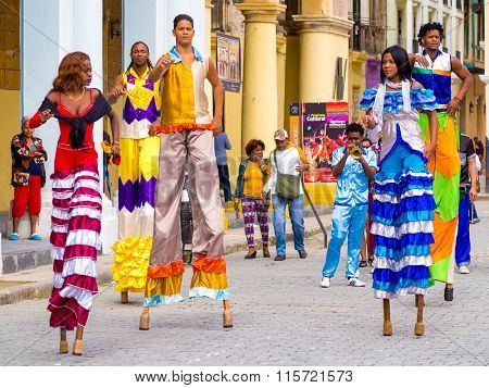 HAVANA,CUBA- JANUARY 24,2015 : Colorful band of street dancers on stilts and musicians on a beautiful Old Havana square