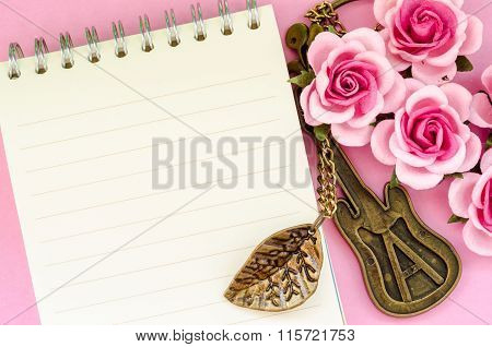 Pink Rose And Open Notebook On Pink Background.