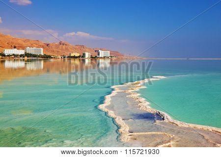 Israeli coast of the Dead Sea. Path from the salt winds picturesquely of salt water. Hotels on the bank are reflected in smooth water