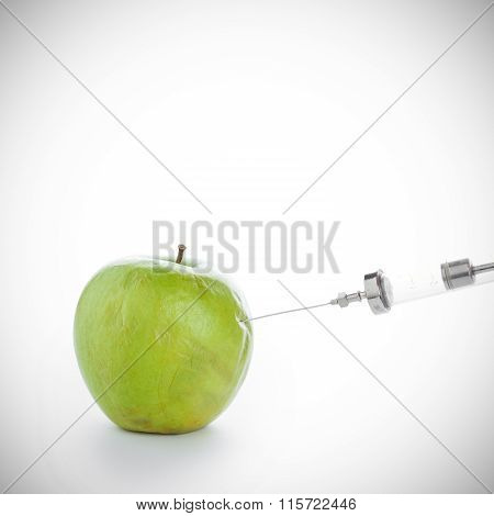 Syringe In Wrinkled Green Apple On White Background