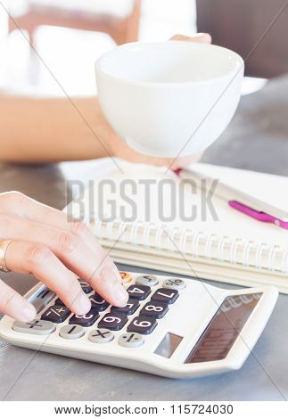 Woman's Hands Holding Coffee Cup And Press Calculator