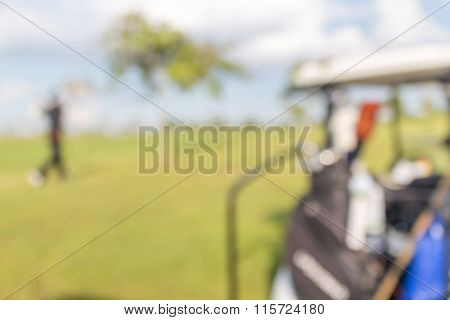 Blurred Photo Of Golfer And Golf Cart In Green Golf Course.