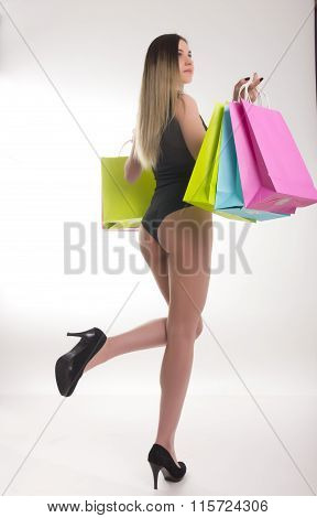 Shopping woman holding shopping bags. Closeup of beautiful women legs in a bathing suit and high hee