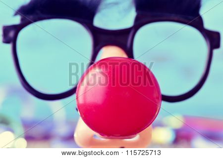 closeup of a pair of fake black glasses with eyebrows and a red clown nose forming the face of a man, against a blue background