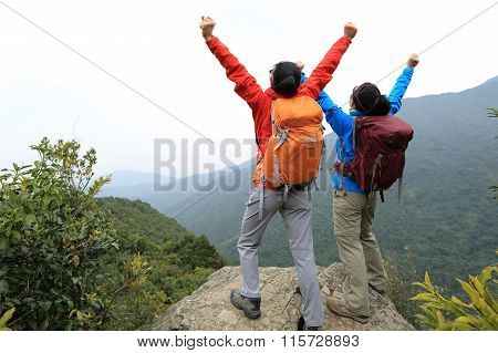 two successful hikers open arms on mountain peak