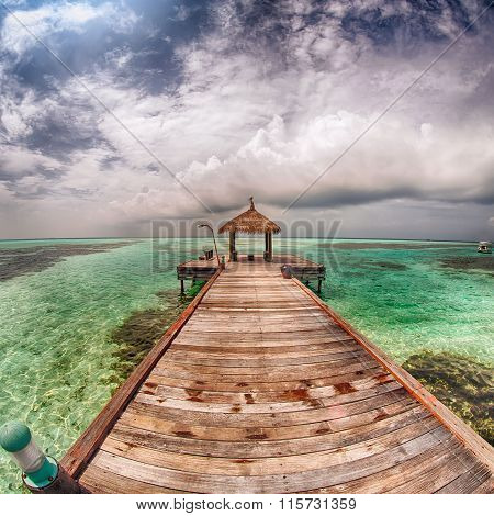Gazebo with a thatched roof stands on the jetty under cloud sky