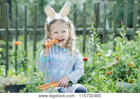 Little blonde girl wearing funny DIY bunny ears gnawing fresh carrot