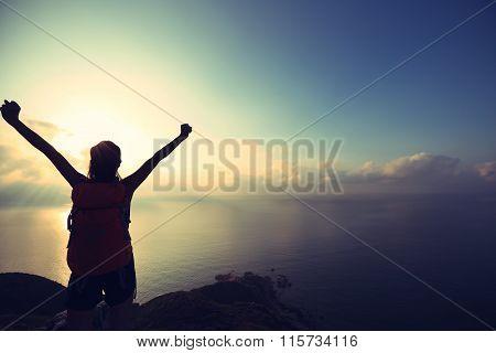 one young woman backpacker hiking on sunrise seaside mountainpeak