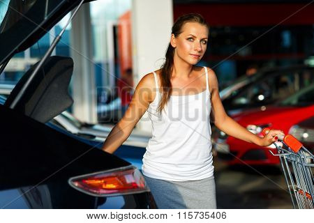 Woman Shifts The Purchase From Shopping Cart In The Trunk Of A Car On The Parking