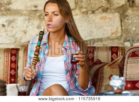 Woman Smoking A Hookah And Drinking Tea In A Cafe, Istanbul, Turkey