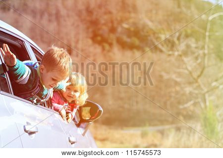 happy little boy and girl travel by car in nature