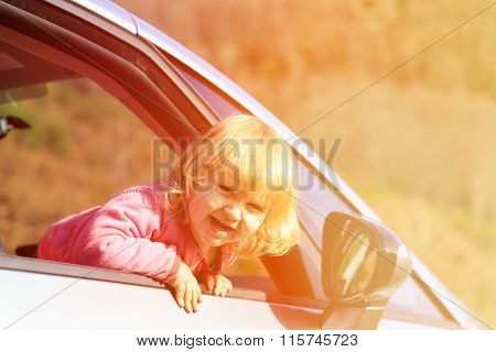 happy little girl travel by car in autumn nature