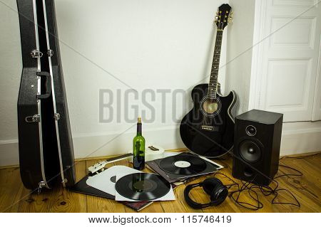 Rock'n'roll Setup With Ukulele, Acoustic Guitar, Speaker, Vinyl Records, Bottle Of Wine And Headphon