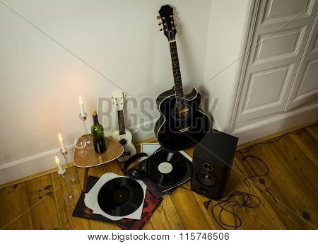 Rock'n'roll Setup With Ukulele, Acoustic Guitar, Speaker, Candles, Vinyl Records, Bottle Of Wine And