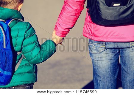 Mother holding hand of little son with backpack on the road