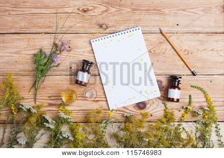 Alternative Medicine Concept - Fragrant Oil In The Bottles, Herbs And Blank Notepad
