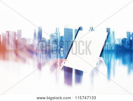 Female hand touching screen of her tablet, blurred city background. Double exposure.